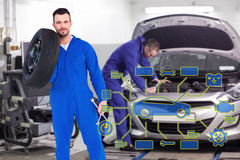 Composite image of smiling male mechanic holding tire Royalty Free Stock Image
