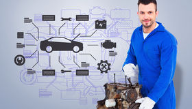 Composite image of smiling male mechanic repairing car engine. Smiling male mechanic repairing car engine against grey vignette Royalty Free Stock Images
