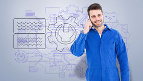 Composite image of smiling male mechanic using mobile phone Royalty Free Stock Photo