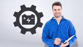 Composite image of smiling male mechanic writing on clipboard. Smiling male mechanic writing on clipboard against grey vignette Royalty Free Stock Photo