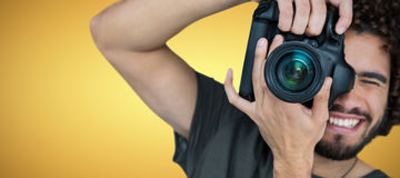 Composite image of smiling male photographer taking picture Royalty Free Stock Image