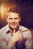 Composite image of smiling man holding a cigar in bar royalty free stock photography