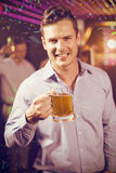 Composite image of smiling man holding glass of beer in bar stock image