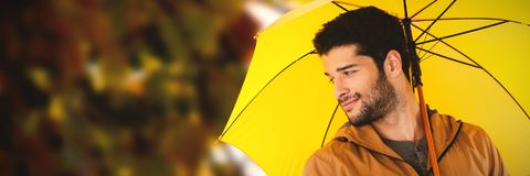 Composite image of smiling man holding yellow umbrella. Smiling man holding yellow umbrella against view of maple leaves Royalty Free Stock Images