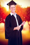 Composite image of a smiling man looking at the camera as he graduates Stock Photo