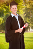 Composite image of a smiling man looking at the camera as he graduates Royalty Free Stock Image