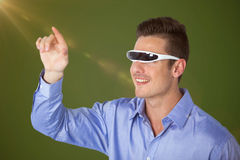 Composite image of smiling man pointing while using virtual video glasses Stock Images