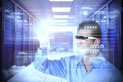 Composite image of smiling man pointing while using virtual video glasses. Smiling man pointing while using virtual video glasses against server room with towers Royalty Free Stock Image