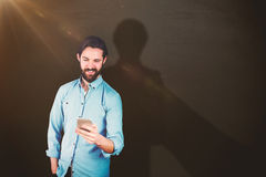 Composite image of smiling man using mobile phone. Smiling man using mobile phone against blackboard Stock Photography