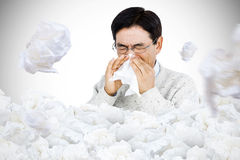 Composite image of smiling man using a tissue Royalty Free Stock Images