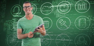 Composite image of smiling man wearing glasses while holding digital tablet Royalty Free Stock Photos