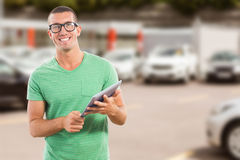 Composite image of smiling man wearing glasses while holding digital tablet Royalty Free Stock Photography