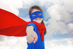 Composite image of smiling masked girl pretending to be superhero Stock Images