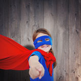 Composite image of smiling masked girl pretending to be superhero Royalty Free Stock Image