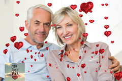 Composite image of smiling mature couple sitting on sofa with arm around Stock Photos