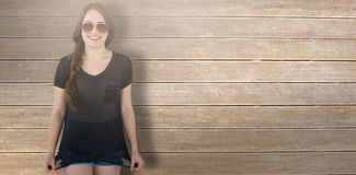 Composite image of smiling model wearing sunglasses stretching top. Smiling model wearing sunglasses stretching top against wooden surface with planks Royalty Free Stock Image