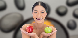 Composite image of smiling natural brunette holding apples in both hands Stock Photos
