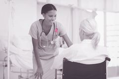 Composite image of smiling nurse assisting female patient in wheelchair Stock Photography