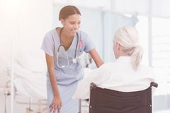 Composite image of smiling nurse assisting female patient in wheelchair Royalty Free Stock Image