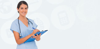 Composite image of smiling nurse writing Royalty Free Stock Photo