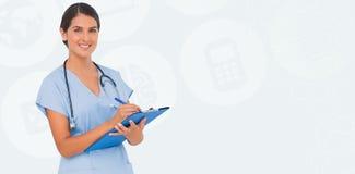 Composite image of smiling nurse writing Royalty Free Stock Photo