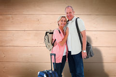 Composite image of smiling older couple going on their holidays Stock Image