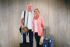 Composite image of smiling older couple going on their holidays Royalty Free Stock Photography