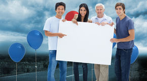 Composite image of smiling people holding and showing a big sign Stock Photos