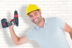 Composite image of smiling repairman holding power drill. Smiling repairman holding power drill against white wall Stock Photo
