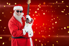 Composite image of smiling santa claus playing a guitar Royalty Free Stock Photos