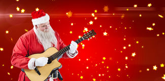 Composite image of smiling santa claus playing guitar Royalty Free Stock Photography