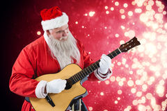 Composite image of smiling santa claus playing guitar Stock Image