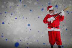 Composite image of smiling santa claus playing guitar Stock Photos