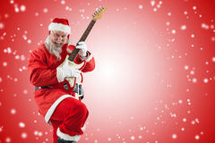 Composite image of smiling santa claus playing guitar while dancing Royalty Free Stock Photos