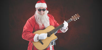 Composite image of smiling santa claus playing guitar while standing Royalty Free Stock Images