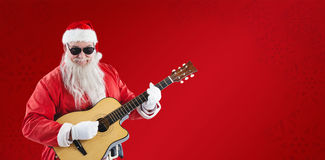 Composite image of smiling santa claus playing guitar while standing Royalty Free Stock Image