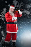 Composite image of smiling santa claus playing violin Royalty Free Stock Photos