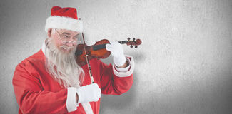 Composite image of smiling santa claus playing violin Stock Image