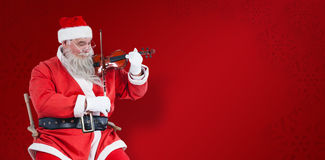 Composite image of smiling santa claus playing violin on chair Stock Photos