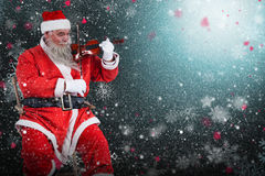 Composite image of smiling santa claus playing violin on chair Royalty Free Stock Photography