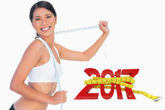 Composite image of smiling slim woman playing with her measuring tape stock images