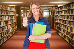 Composite image of smiling student holding notebook and file. Smiling student holding notebook and file  against entrance of the college library Stock Photos