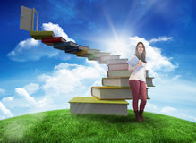 Composite image of smiling student holding textbook Stock Photo