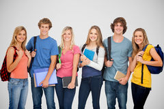 Composite image of smiling students all geared up for college Royalty Free Stock Photography