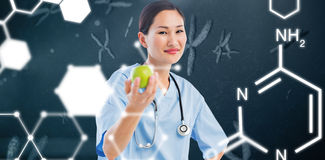 Composite image of smiling surgeon holding an apple with colleague in hospital. Smiling surgeon holding an apple with colleague in hospital against medical icons Stock Images