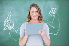 Composite image of smiling teacher using digital tablet in front of blackboard. Smiling teacher using digital tablet in front of blackboard against digital image Royalty Free Stock Photography