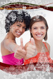 Composite image of smiling teenage girls proudly showing their thumbs up against a white background Royalty Free Stock Image