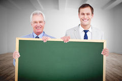 Composite image of smiling tradesmen holding blank sign Stock Photos