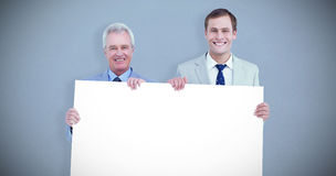 Composite image of smiling tradesmen holding blank sign Royalty Free Stock Images