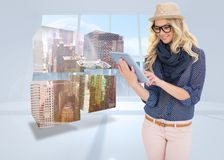 Composite image of smiling trendy blonde using tablet computer Royalty Free Stock Photo